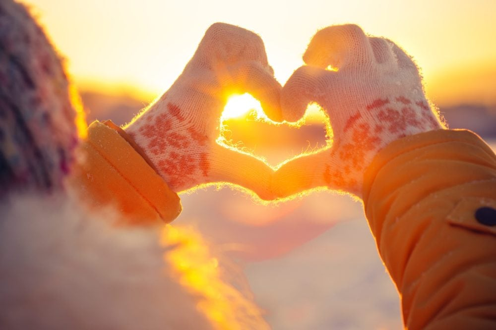 Woman making a heart shape with her gloved hands in winter