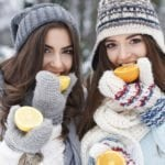 two attractive women in winter clothes eating oranges with a winter scene in the background